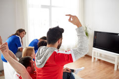 Friends or football fans watching tv at home. Friendship, leisure, sport, people and entertainment concept - happy friends or football fans watching soccer on tv Stock Photo