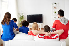 Friends or football fans watching tv at home. Friendship, leisure, sport, people and entertainment concept - happy friends or football fans watching soccer on tv Royalty Free Stock Photography