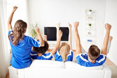 Friends or football fans watching tv at home. Friendship, leisure, sport, people and entertainment concept - happy friends or football fans watching soccer on tv Stock Photography
