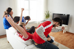 Friends or football fans watching tv at home. Friendship, leisure, sport, people and entertainment concept - happy friends or football fans watching soccer on tv Stock Image