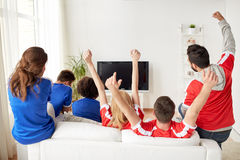 Friends or football fans watching tv at home. Friendship, leisure, sport, people and entertainment concept - happy friends or football fans watching soccer on tv Royalty Free Stock Photos