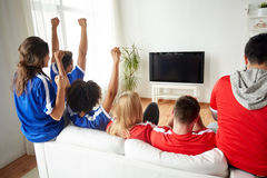 Friends or football fans watching tv at home. Friendship, leisure, sport, people and entertainment concept - happy friends or football fans watching soccer on tv Stock Photos