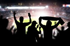 Friends at football game in soccer stadium. Crowd cheering and celebrating a goal in arena during match. Silhouette people in live sport audience having fun royalty free stock images
