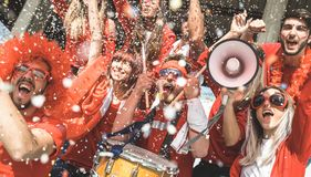 Friends football supporter fans cheering with confetti watching. Soccer match event at stadium - Young people having excited fun on sport world championship stock image