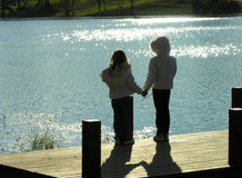 Friends forever. Two girls holding hands on a boat dock at the lake in winter Royalty Free Stock Photos