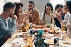 Friends forever. Group of young people in casual wear eating pizza and smiling while having a dinner party indoors stock image