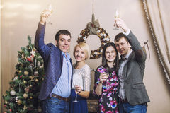 Friends of four men and women with bacale celebrate with champag Royalty Free Stock Photography