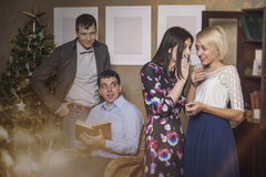 Friends of four men and women going and whispering in the interi Royalty Free Stock Photo