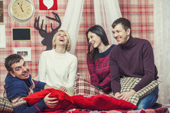 Friends of four men and women laughing and talking in the bedroo Stock Images