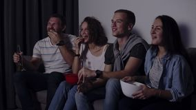 Friends of four sit on couch, watch funny film on TV. Caucasian young group sit on the couch, drinks and snacks - stock video