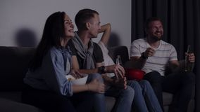 Friends of four sit on couch, watch funny film on TV. Caucasian young group sit on the couch, drinks and snacks. Movie stock footage