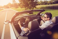 Friends, friendship, destination, auto vehicle rent, escape, speed ride. Rear back shot of carefree wife driver with arms rudder. And henpecked husband on way stock photos