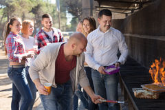 Friends frying meat outdoors Royalty Free Stock Photography
