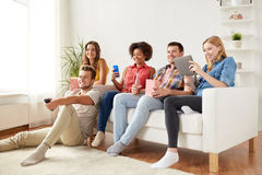 Friends with gadgets and beer watching tv at home. Friendship, people, technology and entertainment concept - happy friends with tablet pc computer and Royalty Free Stock Image