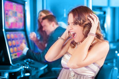 Friends gambling on slot machine. Friends gambling in Casino on slot machine, a women is winning Royalty Free Stock Photography