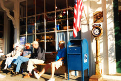 Friends gather for a good chat. Folks enjoy the nice weather outside a General Store royalty free stock image