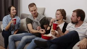 Friends are gathering together and having fun at the living room with loft interior. Male and female company, The girl. With a big red bowl with popcorn stock video