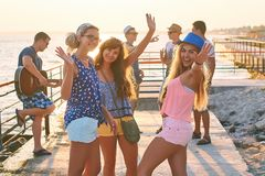 Friends hanging out at the sunny summer seaside. Friends gesturing hi five while hanging out at the seaside royalty free stock photography