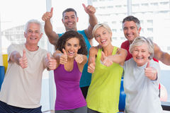 Friends gesturing thumbs up in fitness club. Portrait of happy friends gesturing thumbs up in fitness club Stock Image