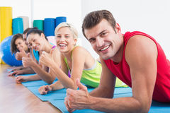 Friends gesturing thumbs up while lying on mats at gym Stock Photo