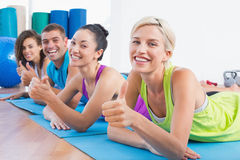 Friends gesturing thumbs up while lying on mats at gym Stock Photography
