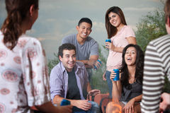Friends Get Together. Group of six happy young people socialize outside Royalty Free Stock Images
