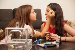Friends getting ready to go out. Hispanic teens getting ready to go out together and putting some makeup on Royalty Free Stock Images