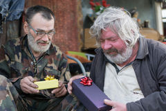 Friends gifts. Slovenly and dirty homeless friends give a gift Stock Images