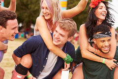 Friends giving piggy backs at a music festival Stock Photography