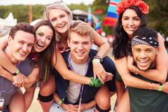 Friends giving piggy backs at a music festival Stock Images