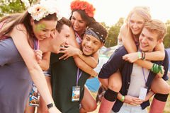 Friends giving piggy backs through music festival campsite Royalty Free Stock Photography
