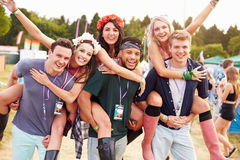 Friends giving piggy backs through music festival campsite Royalty Free Stock Images