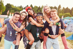 Friends giving piggy backs through music festival campsite Royalty Free Stock Photo
