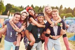 Friends giving piggy backs through music festival campsite royalty free stock photo