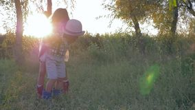 Friends giving piggyback at sunset, little boy and girl play in countryside