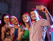 Friends with glasses and smartphone in club Royalty Free Stock Photos