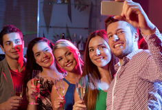 Friends with glasses and smartphone in club Royalty Free Stock Photo