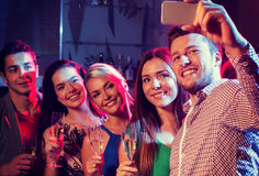 Friends with glasses and smartphone in club Stock Photography