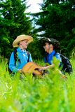 Friends go hiking. Two boys friends go hiking with a guitar and a backpacks. Sunny summer holidays. Outdoor activities stock image