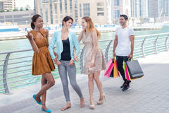 Friends go shopping. Beautiful girls in dresses hug the guy whil Royalty Free Stock Image