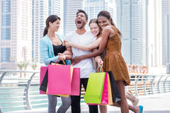 Friends go shopping. Beautiful girls in dresses hug the guy whil Stock Photos
