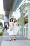 Friends go shopping. Two young women walk on shopping mall with bags stock photo