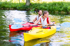 Friends going down river in sport canoe Stock Photos