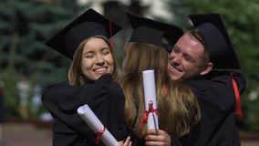 Friends graduates in academic dresses congratulating and hugging each other