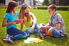 Friends on green lawn. Friendly teenagers resting on green lawn in park Stock Photos