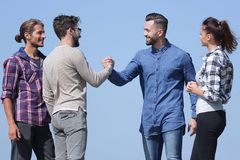 Friends greet each other with a handshake royalty free stock photo