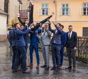 Friends of the groom throw him into the air in front of the church in the Small Square. Sibiu city in Romania. Sibiu, Romania, October 07, 2017 : Friends of the royalty free stock photo