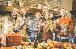 Friends group with santa hat celebrating Christmas time with champagne and sweets food at dinner party - Winter holiday concept royalty free stock photography