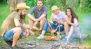Friends group tourist relaxing near bonfire. Hipster roasting sausage while friends speaking sharing impression and royalty free stock photography