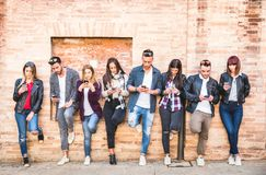 Friends group using smartphone against wall at university college. Backyard break - Young people addicted by mobile smart phone - Technology concept with always royalty free stock images